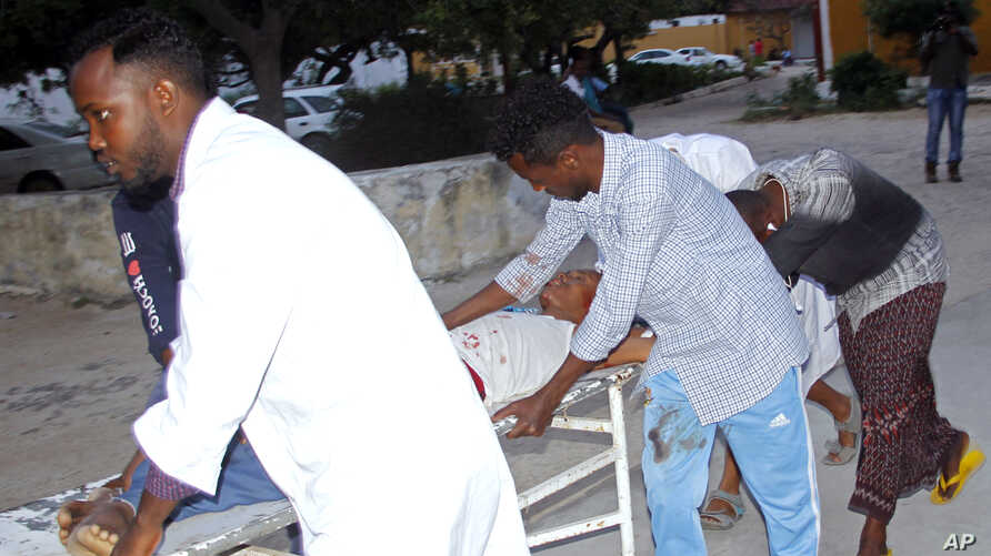 Medical workers help a person on a stretcher who was wounded in a suicide bombing at Madina hospital, Mogadishu, July 24, 2019.