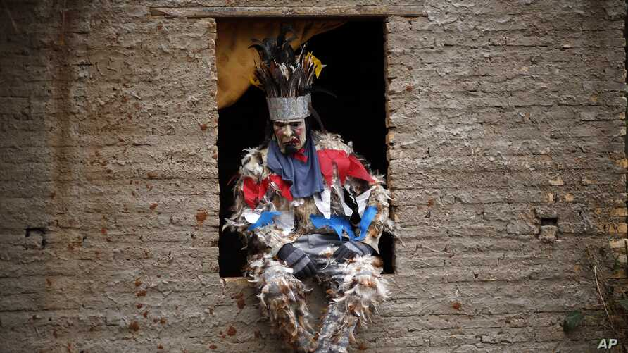 Farmer Genaro Servin sits on a window ledge in his feathered costume during the feast of St. Francis Solano in Emboscada, Paraguay, July 24, 2019.