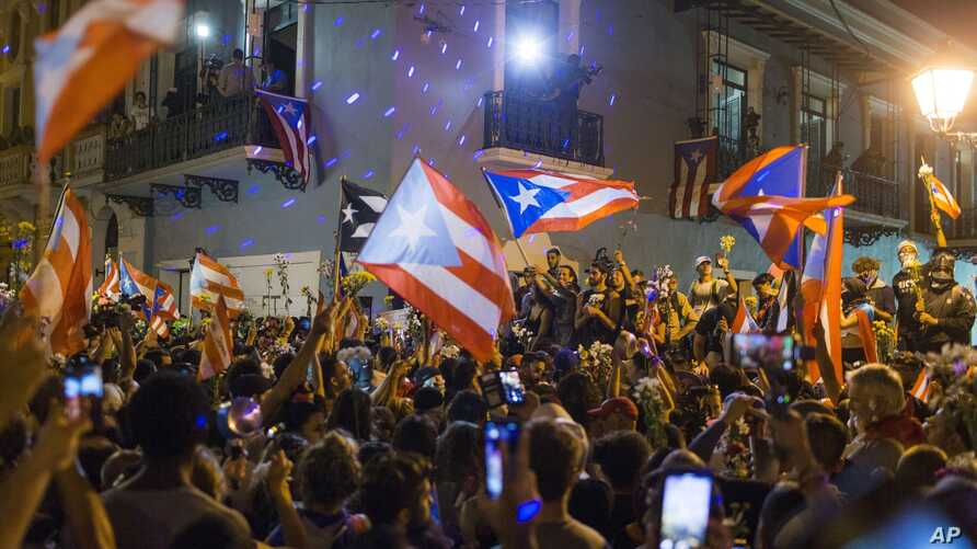 FILE - People celebrate outside the governor's mansion La Fortaleza, after Gov. Ricardo Rossello announced that he is resigning Aug. 2 after nearly two weeks of protests and political upheaval, in San Juan, Puerto Rico, July 25, 2019.