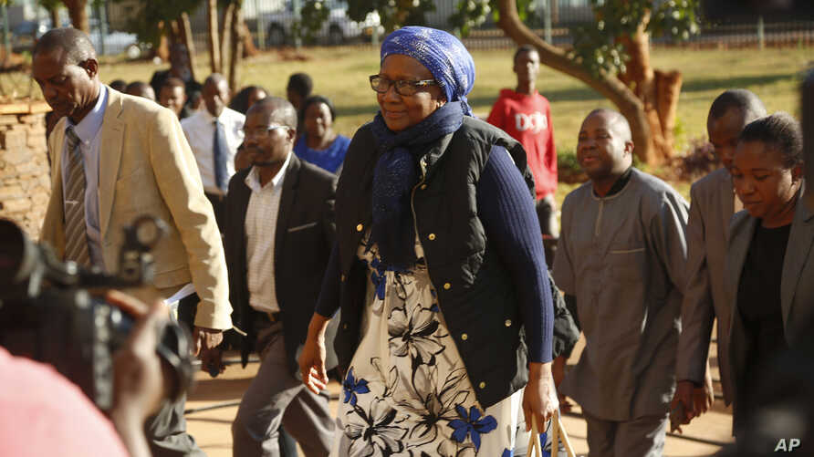 Zimbabwe tourism and environment minister Prisca Mupfumira, center, arrives at court in Harare, July 26, 2019.