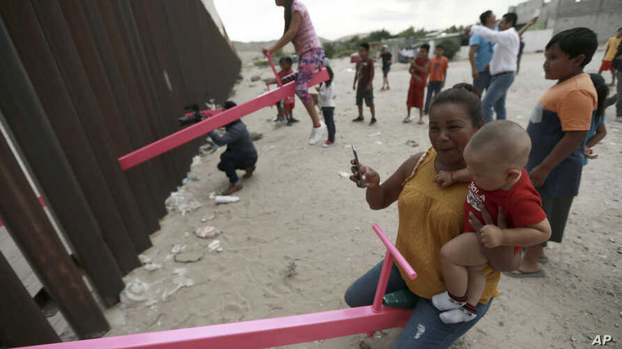 A mother and her baby play on a seesaw installed between the steel fence that divides Mexico from the United States in Ciudad de Juarez, Mexico, July 28, 2019.