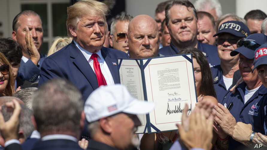 President Donald Trump is surrounded by first responders after signing H.R. 1327, an act ensuring that a victims' compensation fund related to the Sept. 11 attacks never runs out of money, in Washington, July 29, 2019.