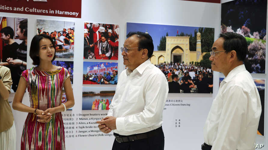 Shohrat Zakir, center, chairman of China's Xinjiang Uighur Autonomous Region, and officials tour a Xinjiang's exhibition before a press conference at the State Council Information Office in Beijing, July 30, 2019.