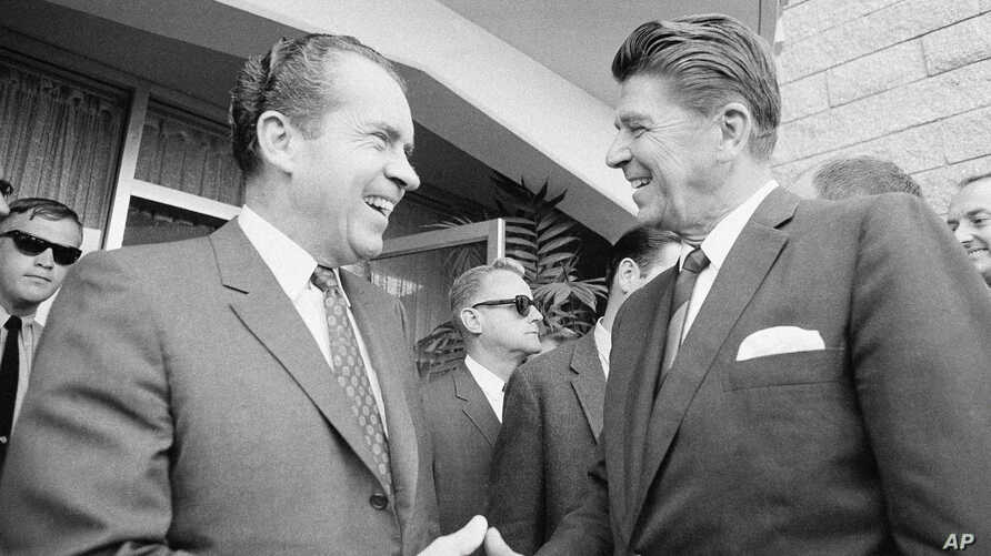 FILE - Richard Nixon greets California Gov. Ronald Reagan (R) in San Diego on Aug. 16, 1968, before conferring about their campaign plans. (AP Photo/Henry Burroughs)