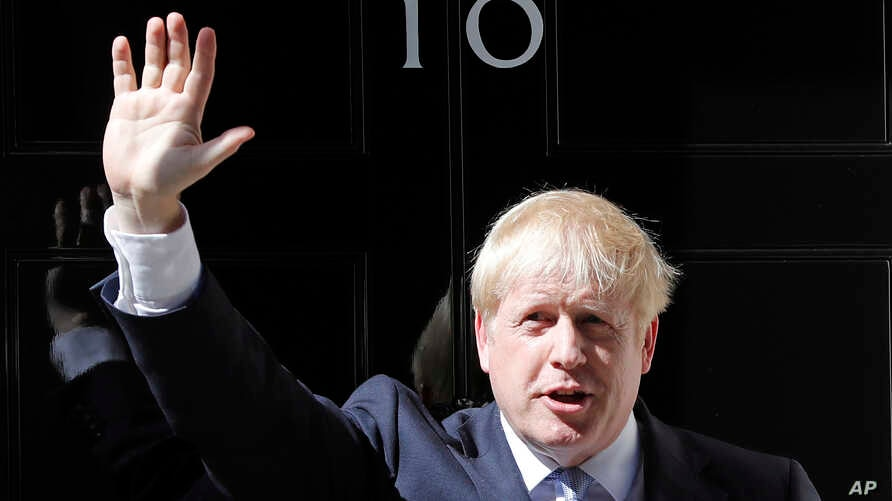 Britain's new Prime Minister Boris Johnson waves from the steps outside 10 Downing Street, London, Wednesday, July 24, 2019.