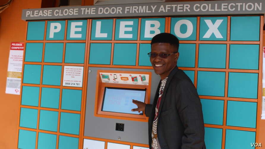 Inventor Neo Hutiri poses in front of one of his Peleboxes. (T. Khumalo/VOA)