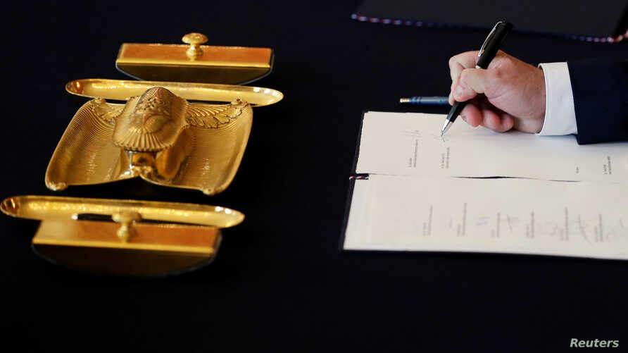 FILE - Czech Culture Minister Antonin Stanek signs a document during the cabinet's inauguration at Prague Castle in Prague, Czech Republic, June 27, 2018.