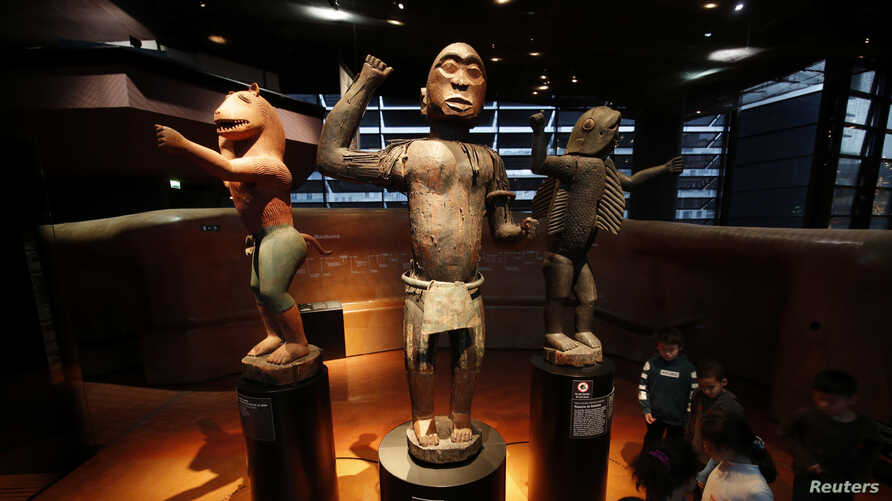 FILE - Three large royal statues of the Kingdom of Dahomey are displayed at the Quai Branly Museum in Paris, France, Nov. 23, 2018.