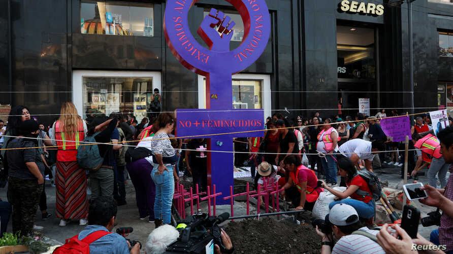 """Activists and relatives place pink crosses at a makeshift monument against femicide with names of the states of Mexico, during a protest against femicide and violence against women, in Mexico City, March 24, 2019. The sign reads: """"No more femicides."""""""