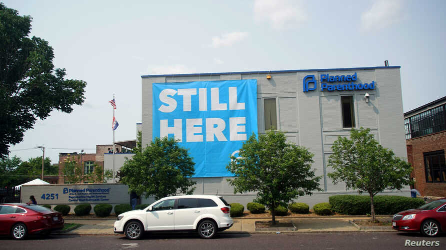 """FILE - A banner stating """"Still here"""" hangs on the side of the Planned Parenthood building in St. Louis, Missouri, May 31, 2019."""