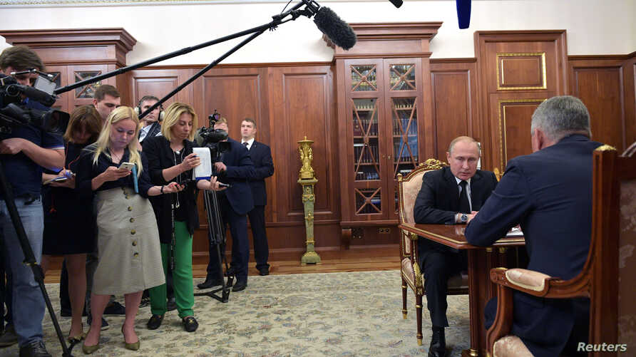 Journalists stand near Russia's President Vladimir Putin as he meets with Defense Minister Sergei Shoigu to discuss a recent incident with a Russian deep-sea submersible, which caught fire in the area of the Barents Sea, in Moscow, Russia, July 2, 2019.