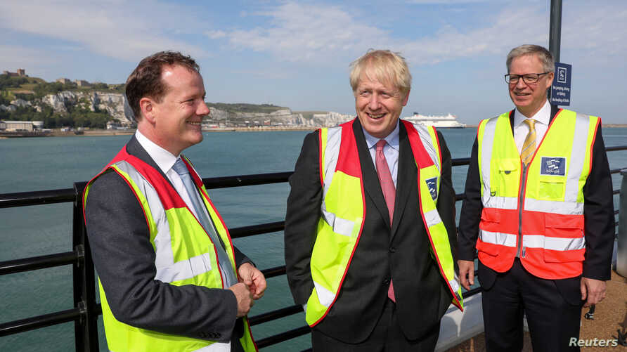 British lawmaker Charlie Elphicke (left) speaks with Boris Johnson, former foreign secretary (C), and Doug Bannister, CEO of Port of Dover Ltd., during a campaign tour in Dover, Britain July 11, 2019.