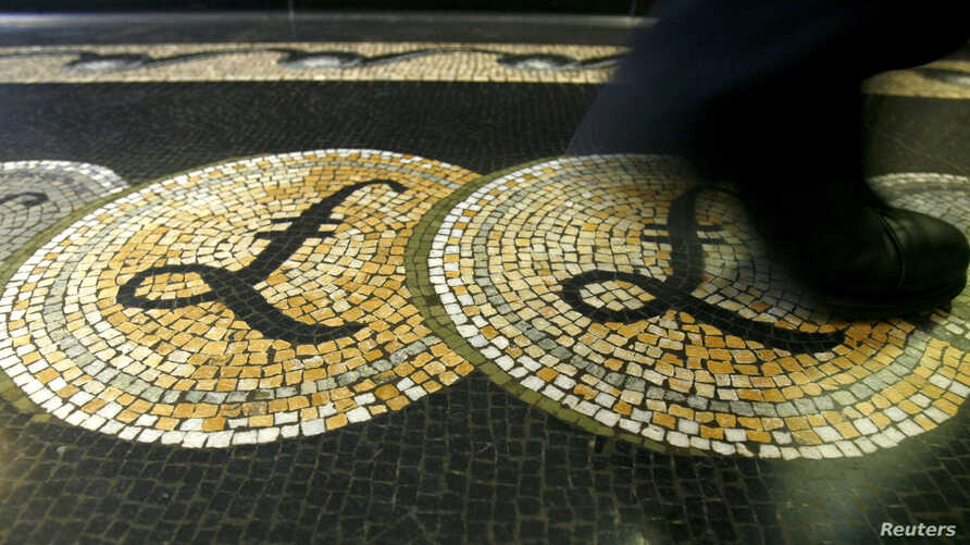 FILE - An employee is seen walking over a mosaic of pound sterling symbols set in the floor of the front hall of the Bank of England in London, Britain.