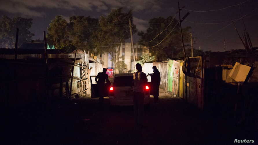 FILE - A man pleads with police officers to release a relative who they have just detained in Dandora during a night patrol in Nairobi, Kenya, Oct. 31, 2015.