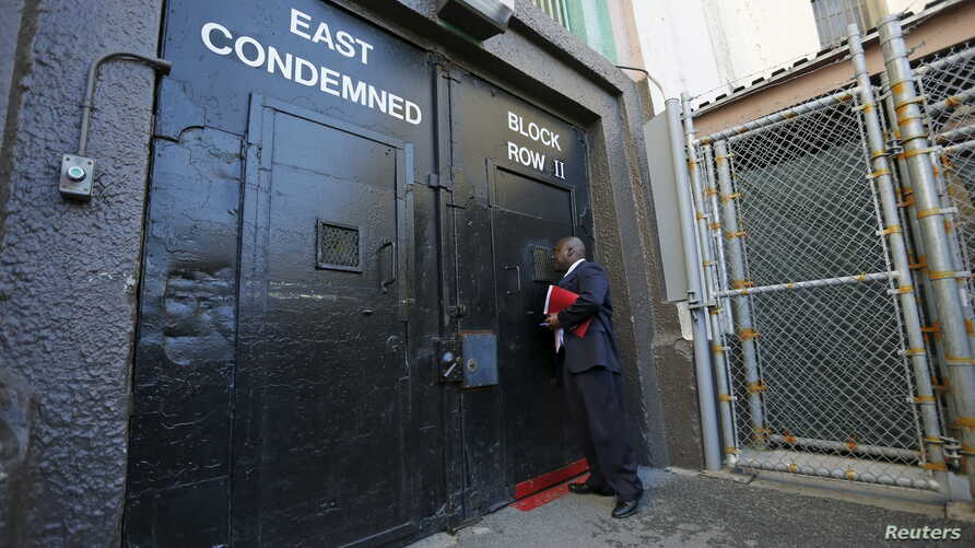 FILE - Lieutenant Sam Robinson, a public information officer at San Quentin State Prison, knocks on the door to the East Block for condemned prisoners during a media tour of California's Death Row in San Quentin, Dec. 29, 2015.