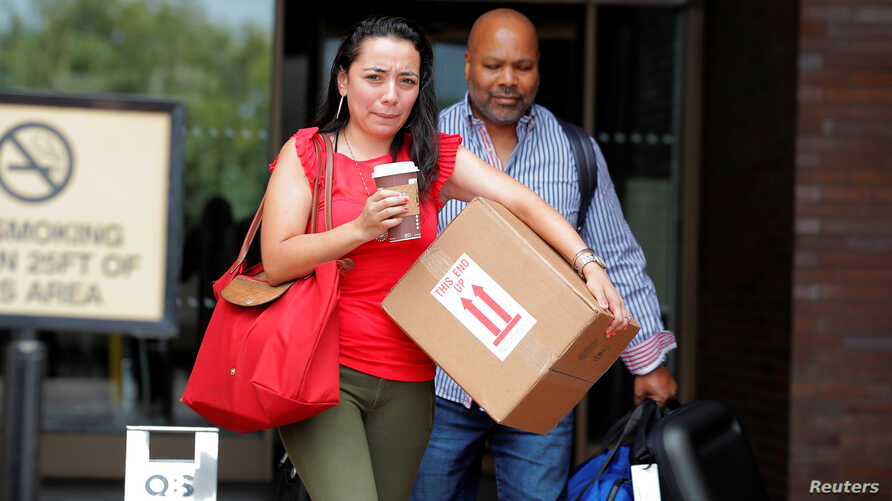 FILE - Former New York Daily News staff members depart the newspaper's Manhattan office after reports that the paper was reducing its editorial staff by some 50 percent in New York, July 23, 2018.