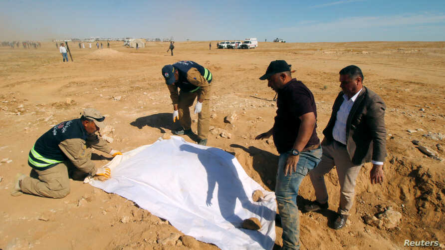 Iraqi members of the Civil Defense cover the bones from an unearthed mass grave of Kurds in west of the city of Samawah, Iraq, April 14, 2019.