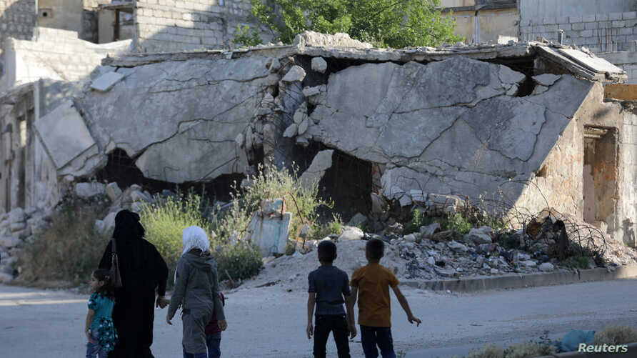 People walk near rubble of damaged buildings in the city of Idlib, Syria, May 27, 2019.