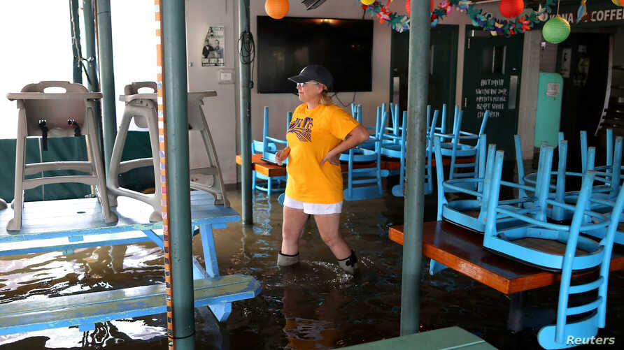 Robyn Iacona-Hilbert walks through her flooded business after Hurricane Barry in Mandeville, La., July 13, 2019.