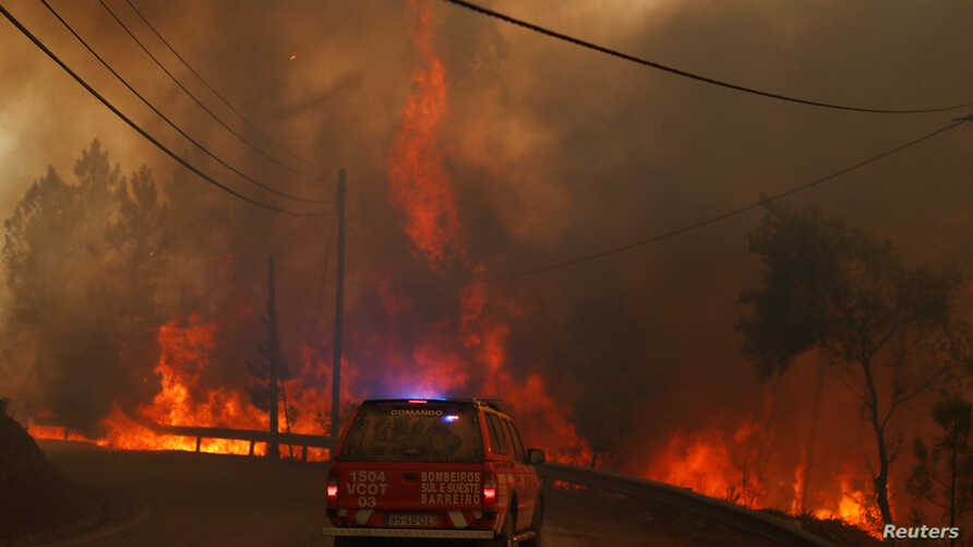 Firefighters drive through smoke from a forest fire in Chaveira, Portugal, July 22, 2019.