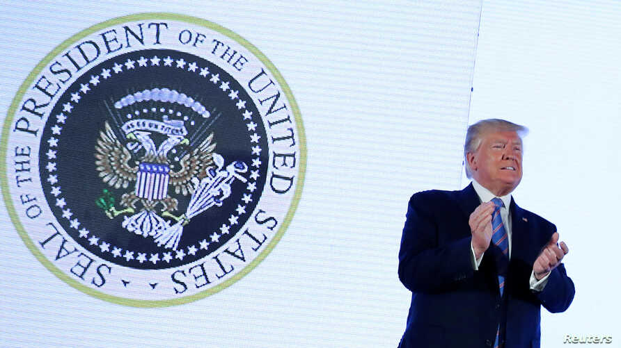 FILE - U.S. President Donald Trump takes the stage next to an altered presidential seal prior to a speech at Turning Point USA's Teen Student Action Summit in Washington, July 23, 2019.