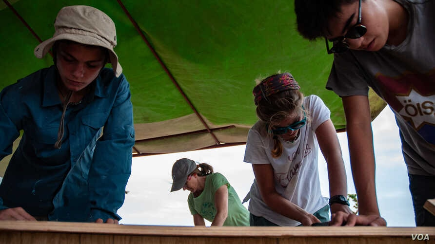 Students and a chaperone from Lick-Wilmerding High School in San Francisco sand desks for a school they helped build in village of Guedj Martin, Senegal.