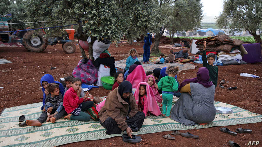 Displaced Syrians gather in a field near a camp for displaced people in the village of Atme, in northern Idlib province, May 8, 2019.