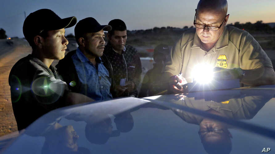 FILE - A U.S. Customs and Border Patrol agent gathers information on four Guatemalan nationals, July 18, 2018, in Yuma, Ariz.