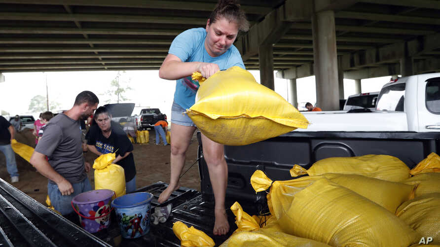 Tiffany Delee tosses a filled sandbag into the back of the family truck, while her husband Mike Delee, left, readies to tie up another bag, in Morgan City, La., July 12, 2019.