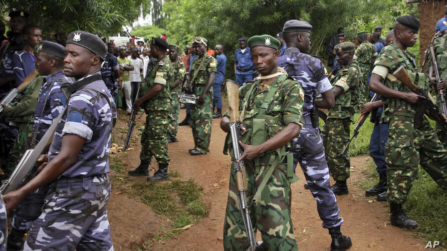 FILE - Amy soldiers and policemen attend the scene where more than 20 people were killed in their homes in an overnight attack in the Ruhagarika community of the rural northwestern province of Cibitoke, in Burundi, May 12, 2018.