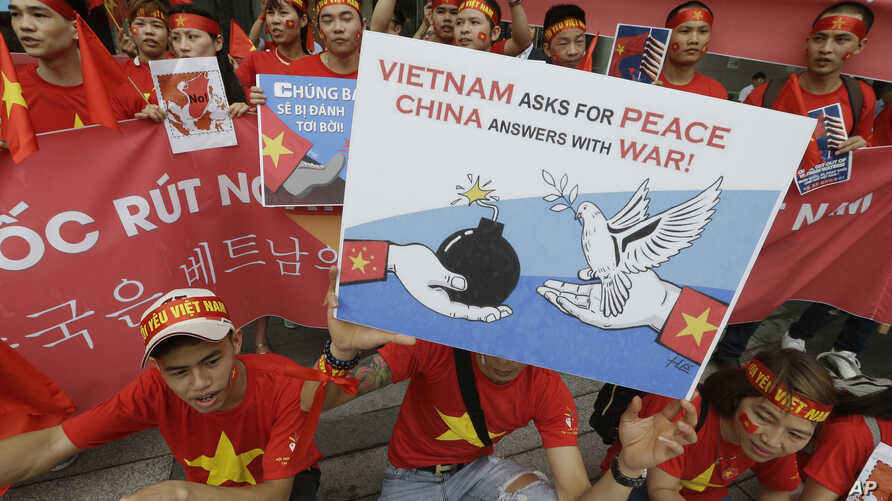 Vietnamese protesters hold up anti-China protest placards during a rally at the Chinese Embassy in Seoul, South Korea, July 24, 2016.
