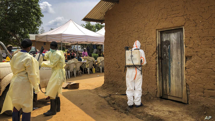 A worker from the World Health Organization decontaminates the doorway of a house on a plot where two cases of Ebola were found, in the village of Mabalako, in eastern Congo, June 17, 2019.