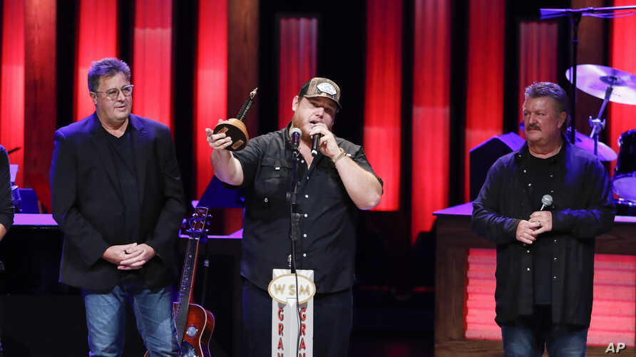 """Vince Gill, left, and Joe Diffie, right, welcome Luke Combs to the Grand Ole Opry at """"Luke Combs Joins the Grand Ole Opry Family,"""" July 16, 2019, in Nashville, Tenn."""