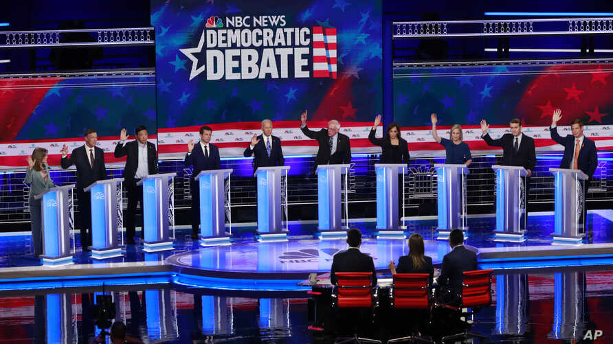 Democratic presidential candidates raise their hands during the Democratic primary debate at the Adrienne Arsht Center for the Performing Arts in Miami, Florida, June 27, 2019.