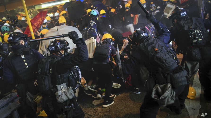 Policemen using batons charge on protesters during a rally in Hong Kong, July 28, 2019.