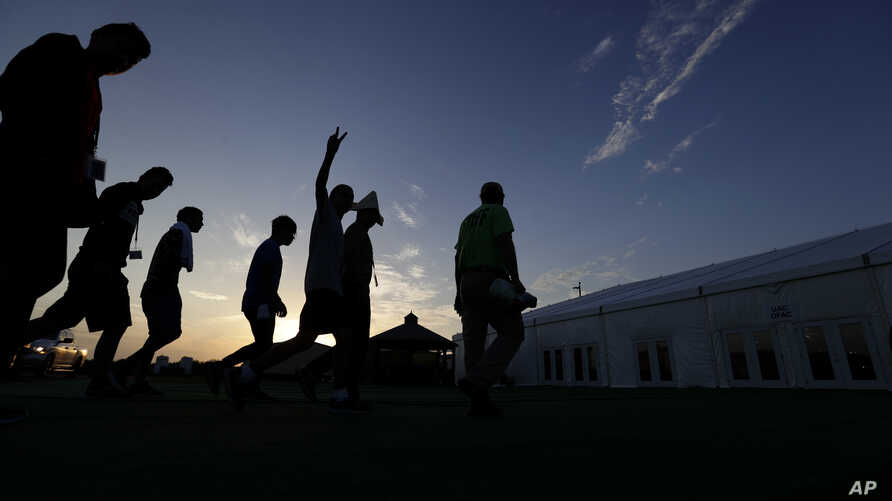 At sunrise, migrants are escorted to a tent that serves a dining hall for the U.S. government's newest holding center for migrant children in Carrizo Springs, Texas, July 9, 2019.