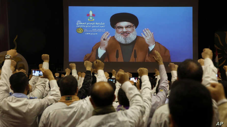 Hezbollah scouts raise their fists and cheer as they listen to a speech of Hezbollah leader Hassan Nasrallah, via a video link, during an annual anniversary rally in southern Beirut, Lebanon, April 22, 2019.