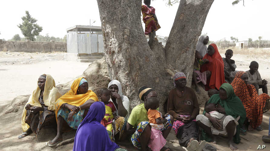 In this photo taken Feb. 18, 2019, Woman and Children displaced by Islamist extremist sits under a tree at Malkohi camp in Yola, Nigeria.