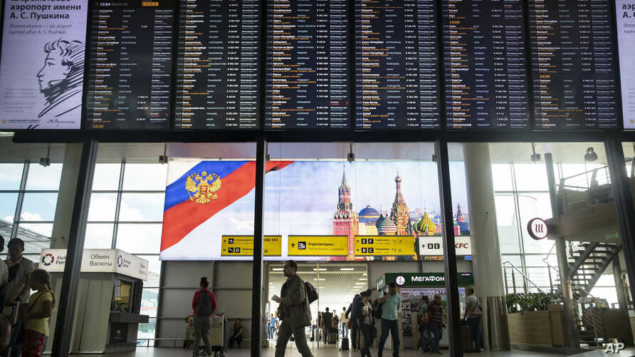 Passengers walk past a departure board at Sheremetyevo international airport in Moscow, Russia, July 8, 2019.