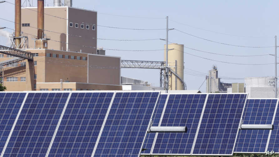 A solar panel array collects sunlight, with the Fremont, Nebraska, May 31, 2018, with a power plant seen behind it.