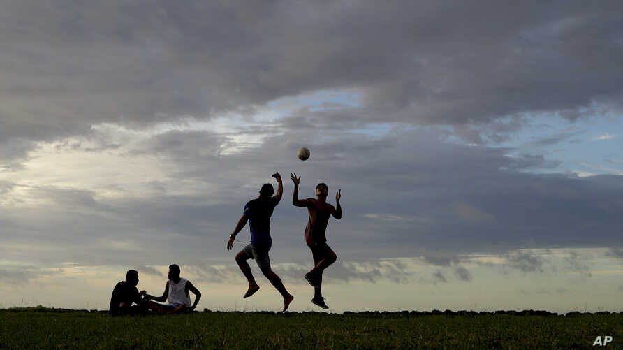 FILE - Young men play a game of rugby at sunset in Nuku'alofa, Tonga.