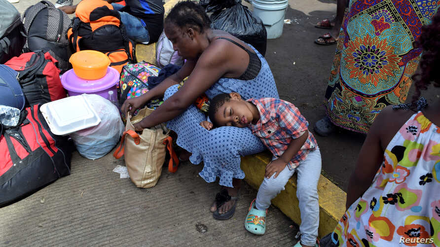 FILE - Migrants from Cameroon rest while waiting with other migrants from Africa and Haiti to request humanitarian visas, issued by the Mexican government, to cross the country towards the United States, in Tapachula, Mexico June 27, 2019.