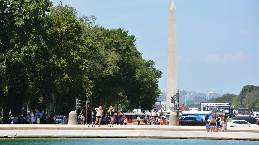 Tourists gather around the Capitol pond with the Washington Monument in the background on a hot day in Washington, DC as temperature rises into the upper 80s Fahrenheit, Friday, July 19, 2019. (Photo by Diaa Bekheet)