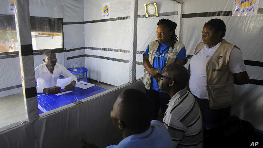 Claude Mabowa Sasi, 21, who had lost his mother, a brother and a sister to Ebola, takes his college-entry exam in an isolation room at an Ebola treatment center in Beni, Congo, July 20, 2019.