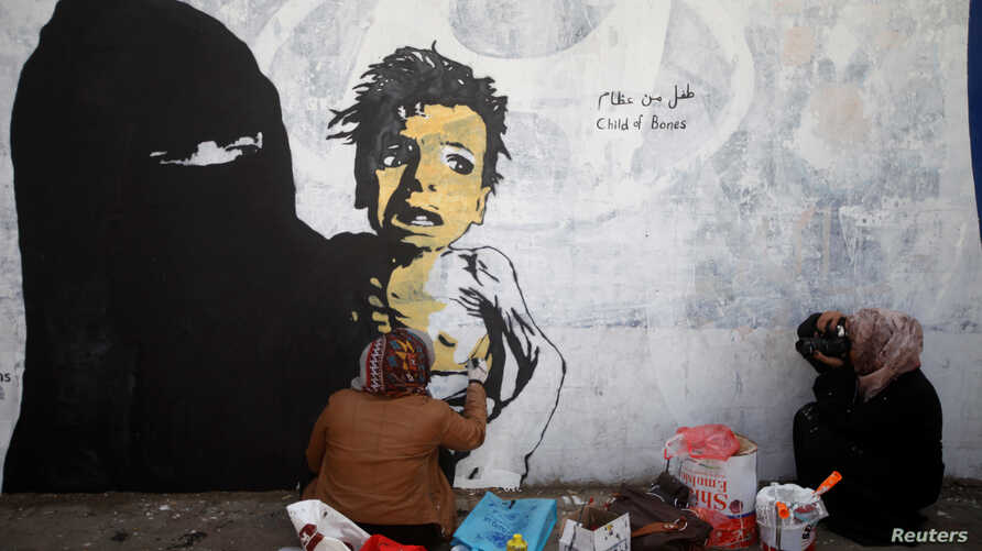 A friend of artist Haifa Subay takes pictures of her painting a mural she says represents the children and women suffering in Yemen's war, in Sanaa, Yemen, Feb. 21, 2019.