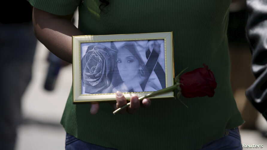FILE - A picture of Andrea Alvarez, whose death is being investigated as a femicide, is displayed during a rally at her funeral march in La Paz, Bolivia, Aug. 22, 2015.
