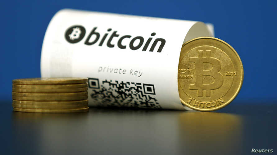 A Bitcoin (virtual currency) paper wallet with QR codes and a coin are seen at La Maison du Bitcoin in Paris, France, May 27, 2015.
