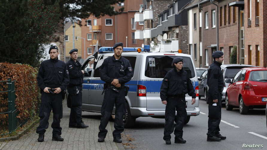 Police stand guard outside as officers investigate a residential building where arrested suspects linked to Paris attacks are thought to live, in Alsdorf near Aachen, Germany, Nov. 17, 2015