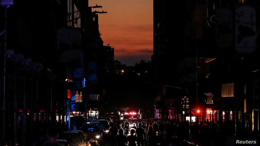 People walk along a dark street near Times Square area, as a blackout affects buildings and traffic during widespread power outages in the Manhattan borough of New York, July 13, 2019.