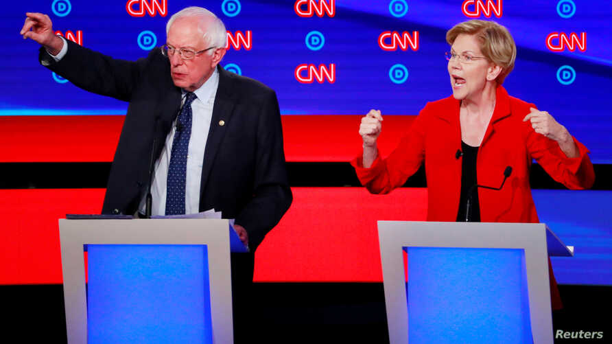 U.S. Senators Bernie Sanders (l) and Elizabeth Warren speak on the first night of the second 2020 Democratic presidential debate in Detroit, Michigan, July 30, 2019.